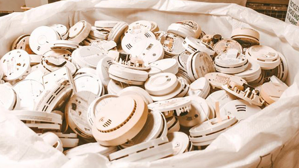 Pile of smoke alarms dropped off for recycling. Recycle unusual products like smoke alarms with our program