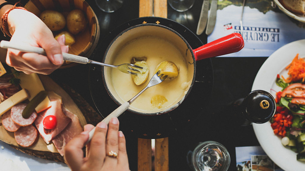 Dipping potatoes into cheese fondue. Fondue fuel is an unusual recyclable product