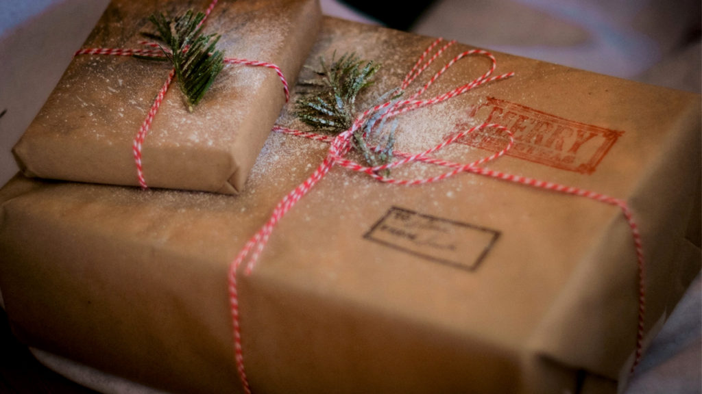 Two gifts wrapped with reused brown paper and ribbon