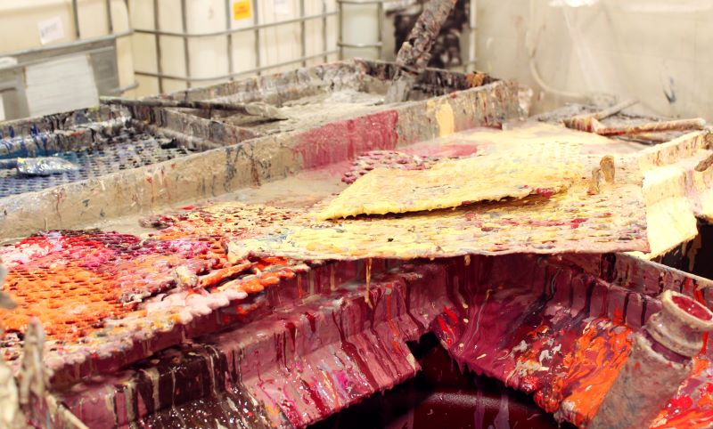 Colourful paint residue on the surface at a paint recycling facility in Delta, BC, Canada