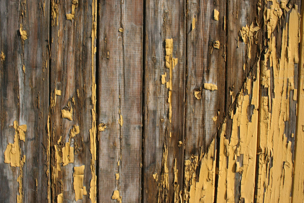 Old yellow paint peeling on a wood deck