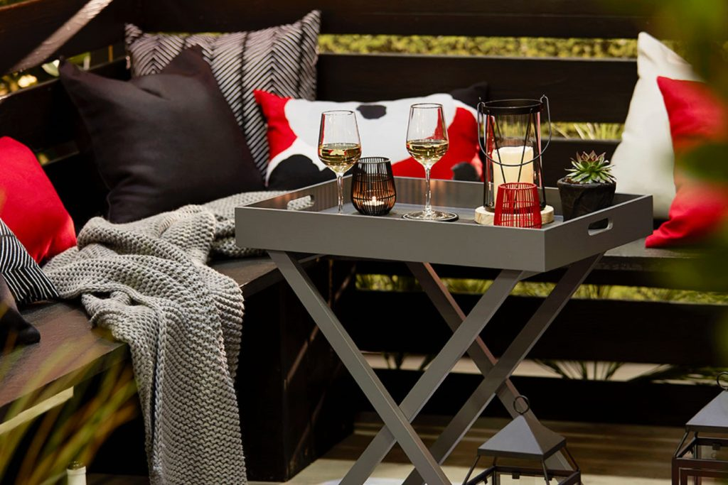 wine on gray tray with pillows and blanket