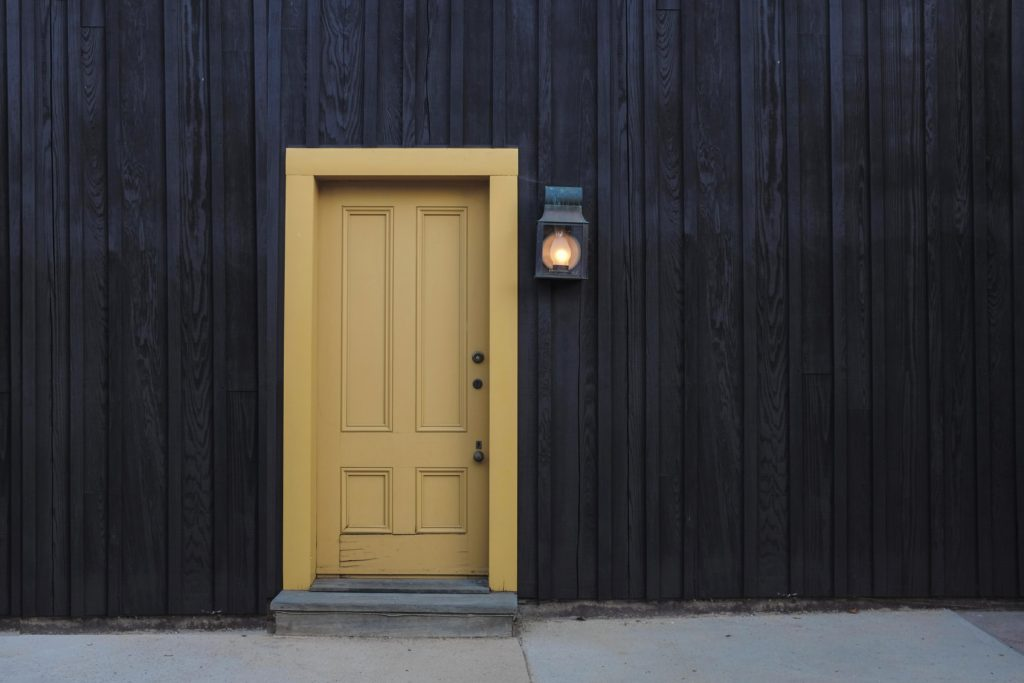 front door painted in yellow with light next to it