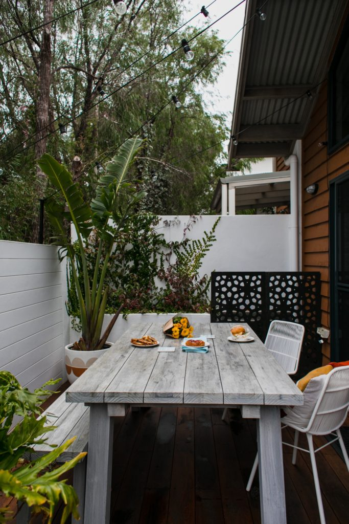 table painted gray and bench on patio with plants