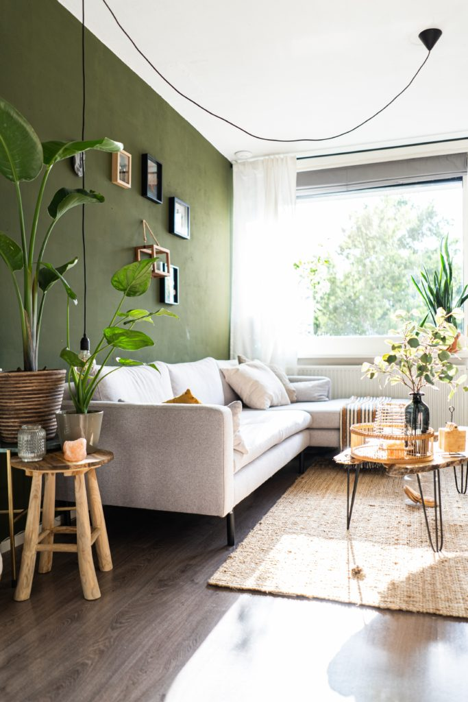 couch and tables with green wall