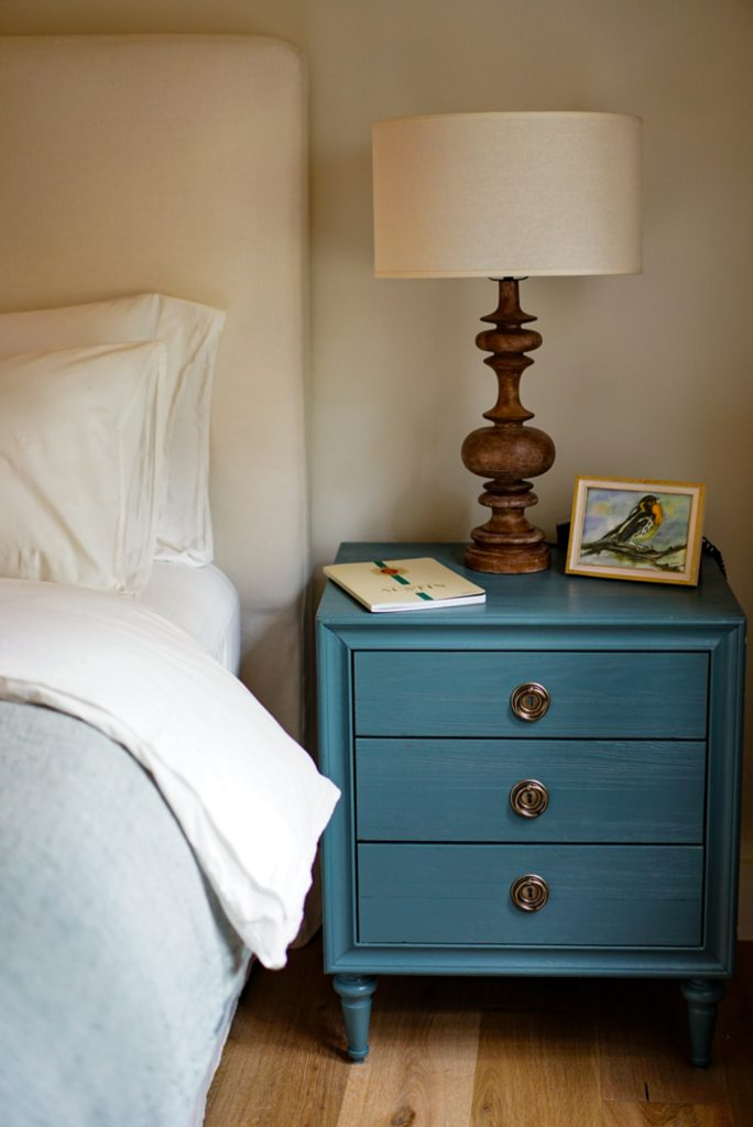 lamp and side table beside bed