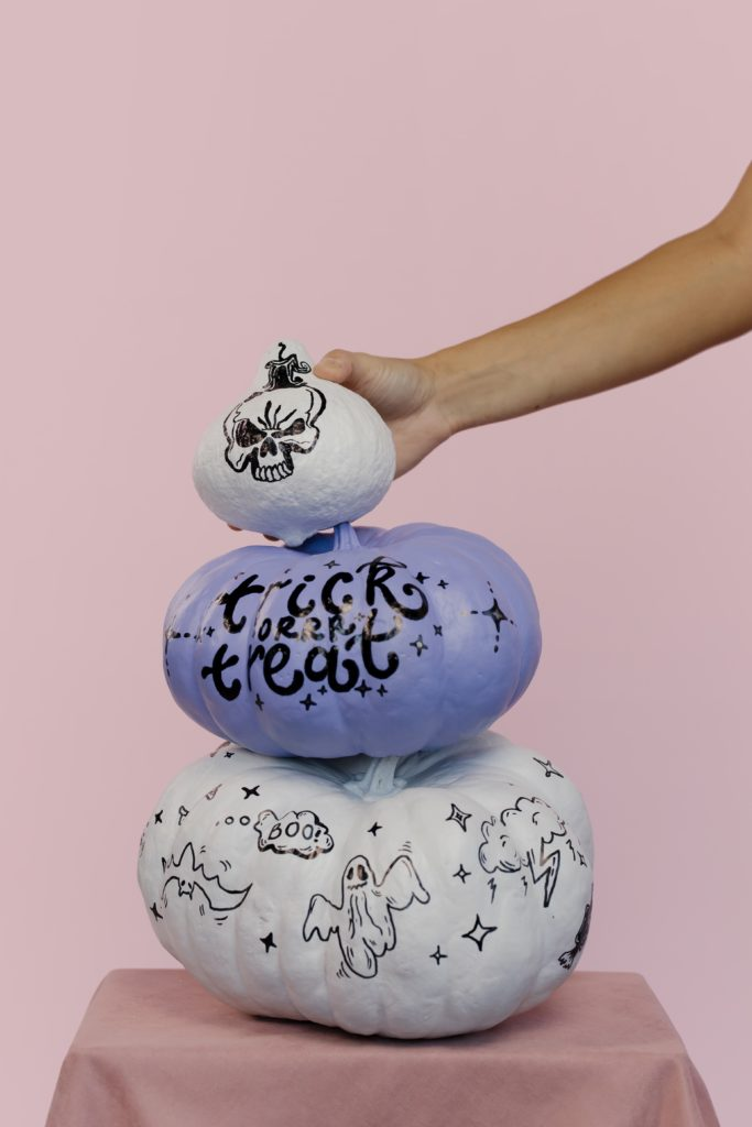 painted pumpkin with hand holding one